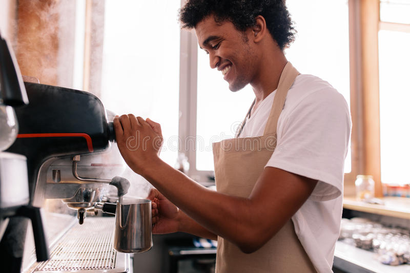 Happy young man preparing coffee at counter stock photos