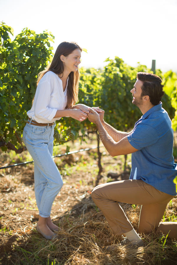 Happy young man proposing his girlfriend at vineyard. During sunny day stock photography