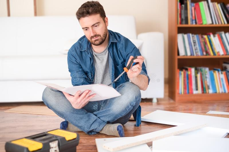 Happy young man reading the instructions to assemble furniture. Man portrait and do it yourself furniture assembly stock photography