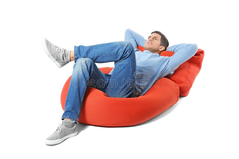 Happy young man relaxing on lounge royalty free stock photography