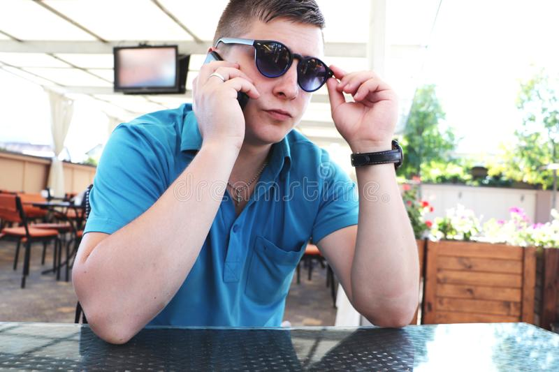 Happy young man satisfied with good mobile connection in roaming while talking with friends on smartphone device. Positive male. Positive male communicating on royalty free stock image
