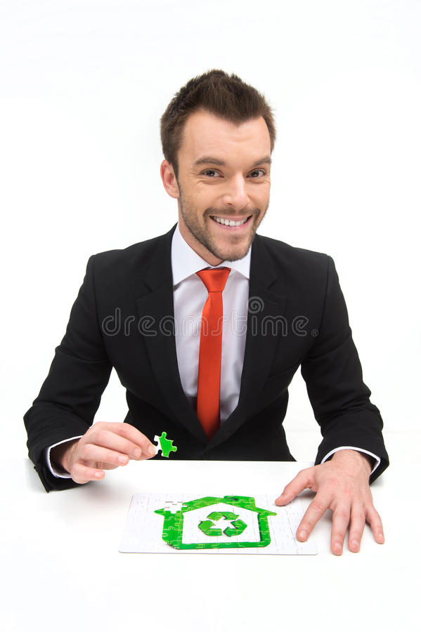 Happy young man in shirt and tie collecting eco puzzle. royalty free stock photos