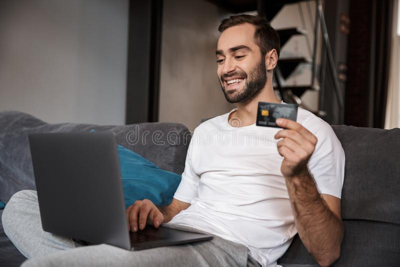 Happy young man sitting on a couch royalty free stock photos