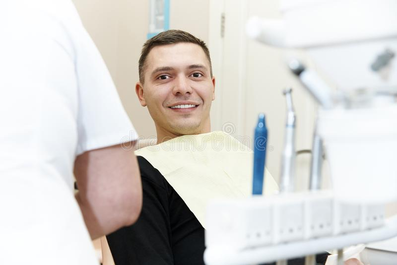 Happy young man in dental chair stock photos