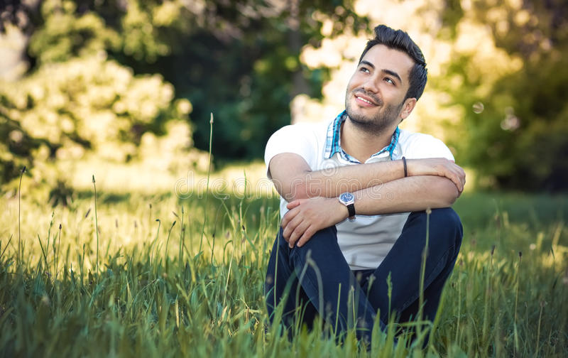 Happy young man sitting on meadow. Gorgeous guy relaxing on grass. Outdoor, daylight stock image