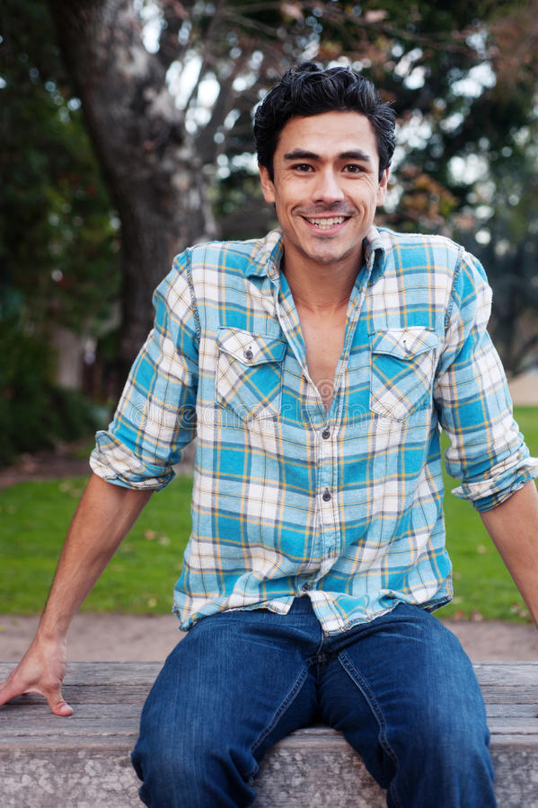 Happy young man sitting in a park royalty free stock images