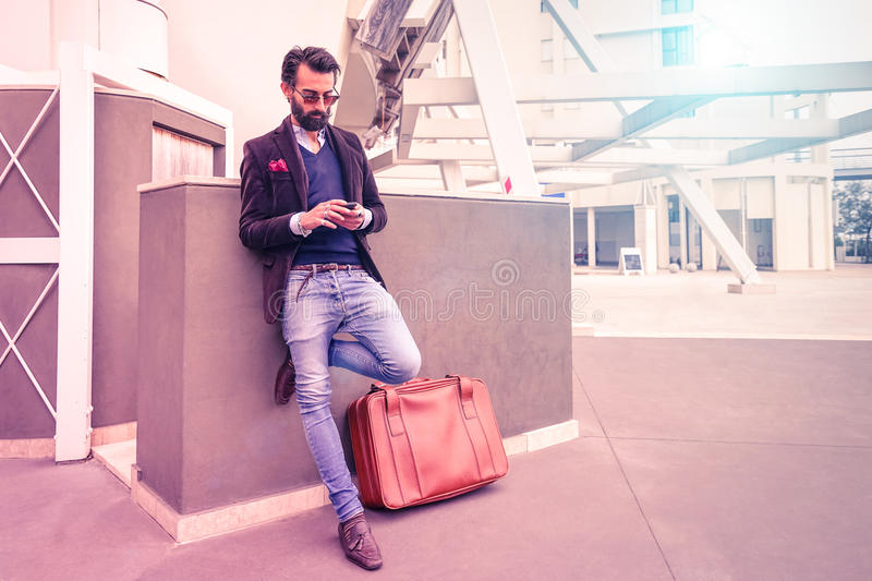 Happy young man with smartphone - Fashion hipster guy using phone royalty free stock image