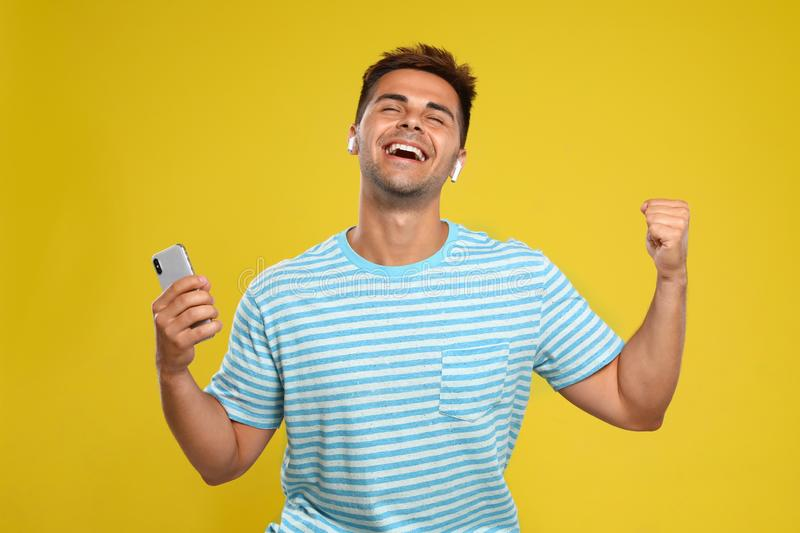 Happy young man with smartphone listening to music through wireless earphones on background royalty free stock image
