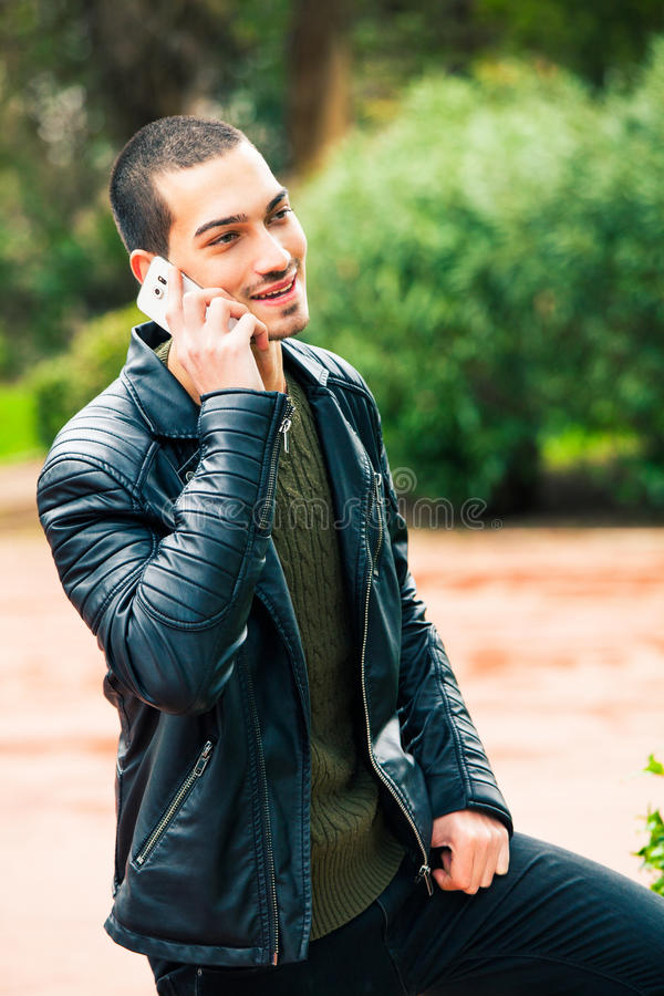 Happy young man with smartphone. Talking on the phone. royalty free stock photography