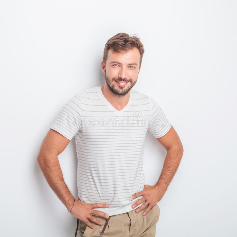 Happy young man smiling. With his hands on hips in studio stock photos