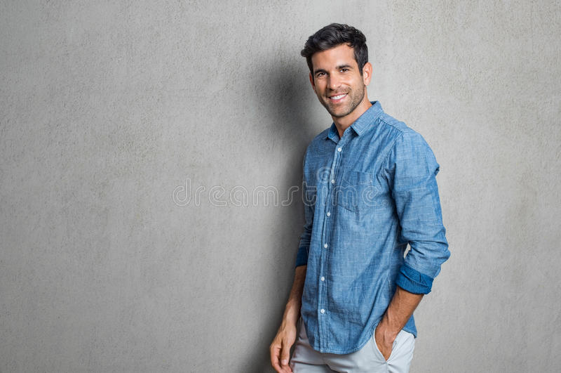 Happy young man. Happy smiling man leaning against grey wall. Portrait of proud mid man isolated on grey background. Young casual hispanic man against grey wall royalty free stock photo