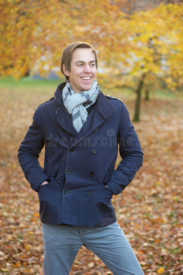 Happy young man smiling outdoors in fall season royalty free stock images
