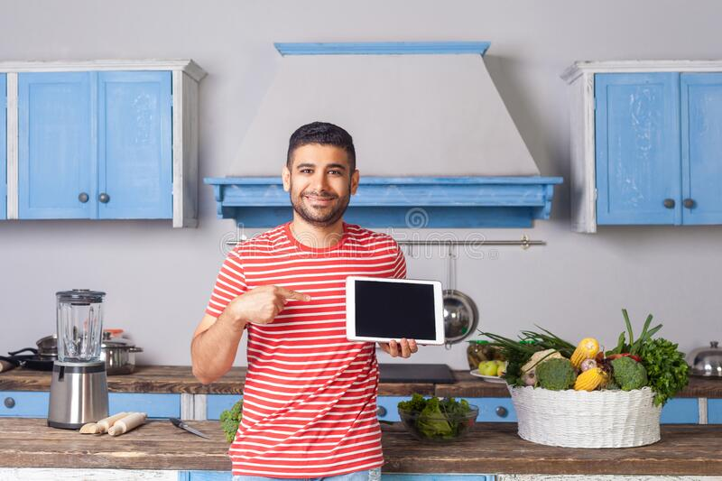 Happy young man standing in kitchen and pointing at tablet, looking at camera with toothy smile. Recommending food recipes from internet, fresh green royalty free stock image