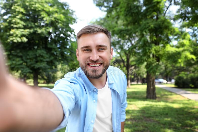 Happy young man taking selfie stock image