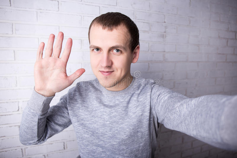 happy young man taking selfie picture or recording video for blog and saluting subscribers stock photography