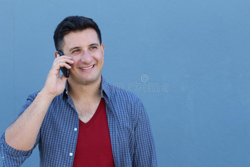 Happy young man talking on cell phone isolated on blue background.  stock image