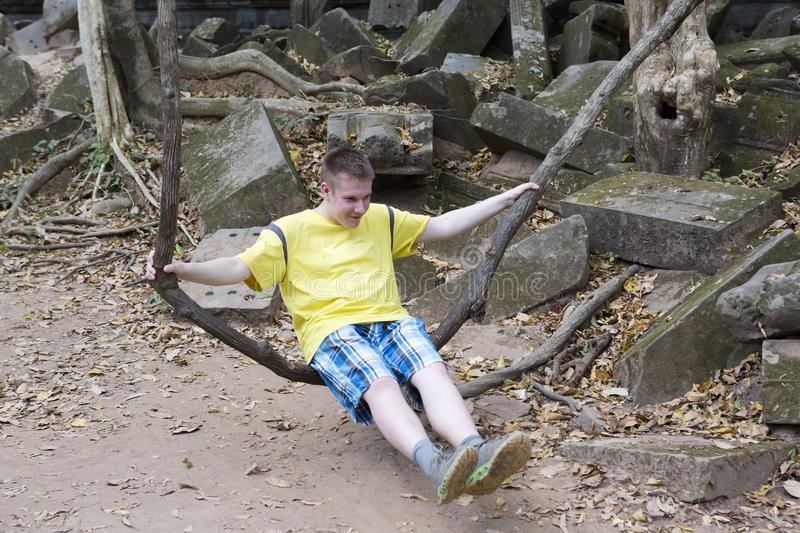Happy young man, the teenager, the tourist, shakes on a liana as on a swing on Beng Mealea temple ruin in the Koh Ker complex, Si royalty free stock images