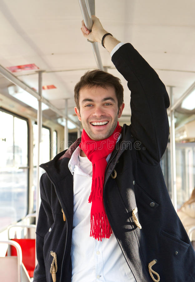 Happy young man traveling with public transport royalty free stock photography
