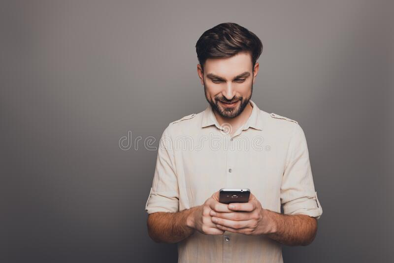 Happy young man typing sms on gray background royalty free stock images