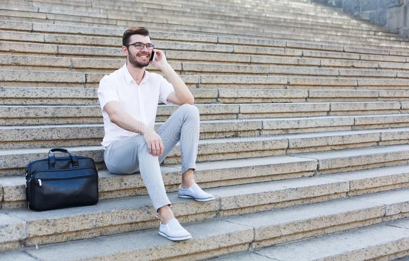 Happy young man using a phone on stairs royalty free stock image