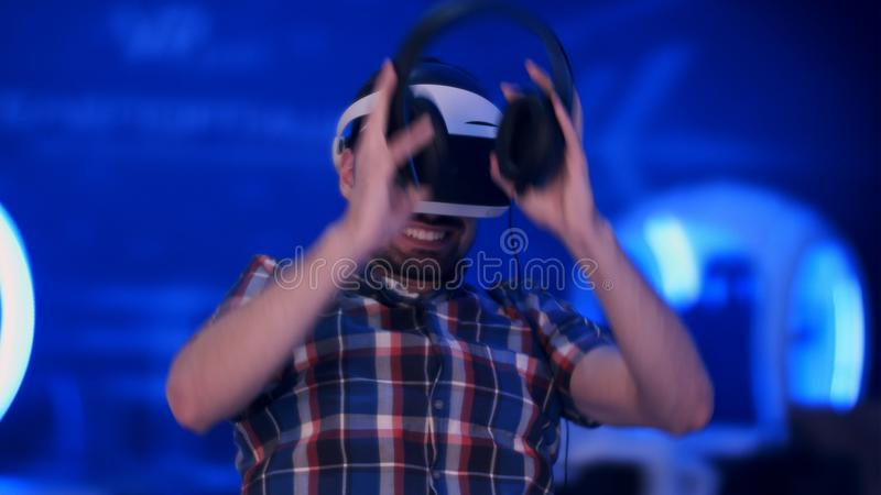 Happy young man with virtual reality headset with controller gamepad playing racing video game stock photos