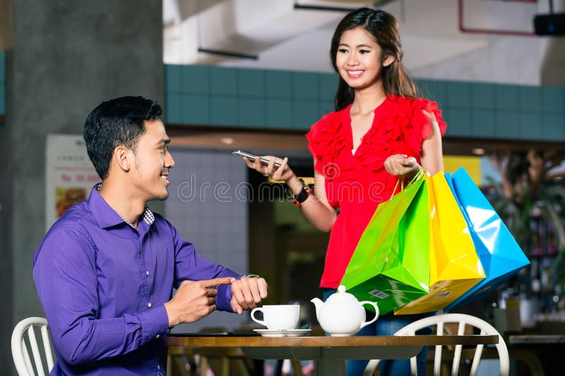 Happy young man waiting for his beautiful girlfriend after shopping royalty free stock image