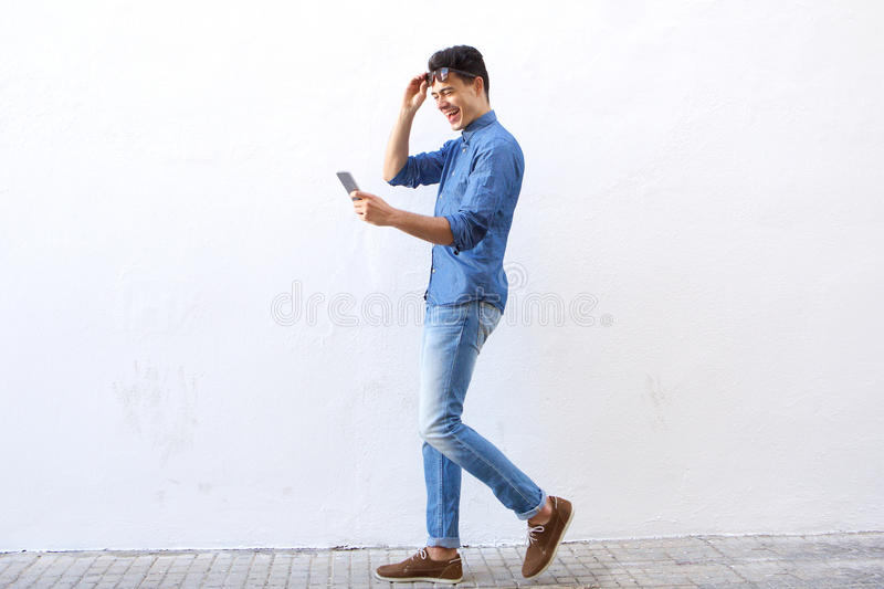 Happy young man walking on street looking at mobile phone. Full length side portrait of a happy young man walking on street looking at mobile phone royalty free stock images