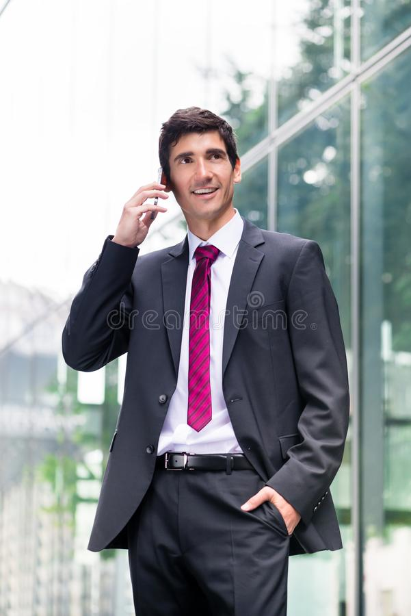 Happy young man wearing business suit while talking on mobile ph. One and walking along a modern corporate building stock photos