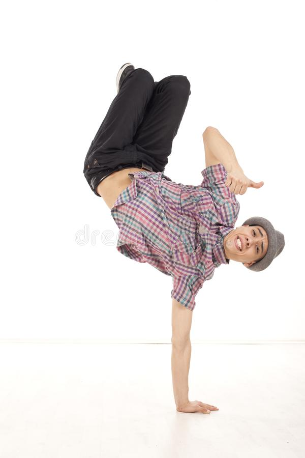 Happy young man wearing casual shirt dancing sitting on one hand. Performing breakdance moves on wood floor upside down, with legs up. OK hand gesture and royalty free stock photography