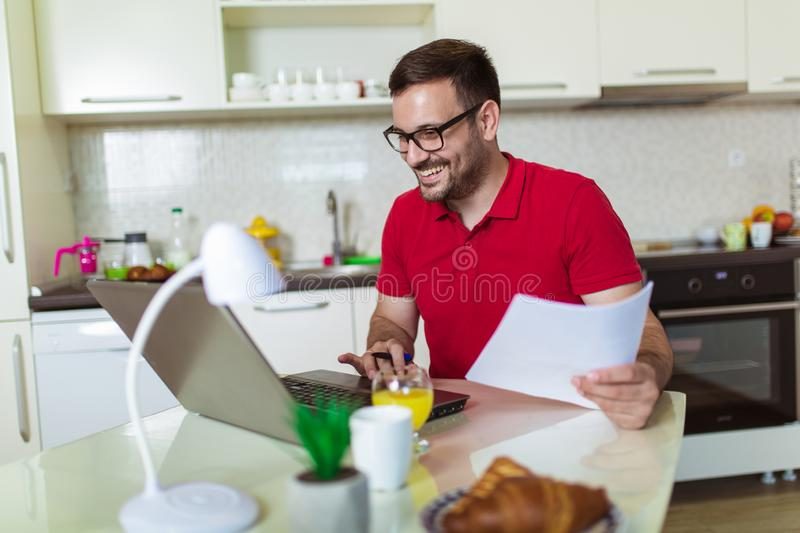 Young man, wearing glasses and smiling, as he works on his laptop to get all his business done early in the morning with his stock images