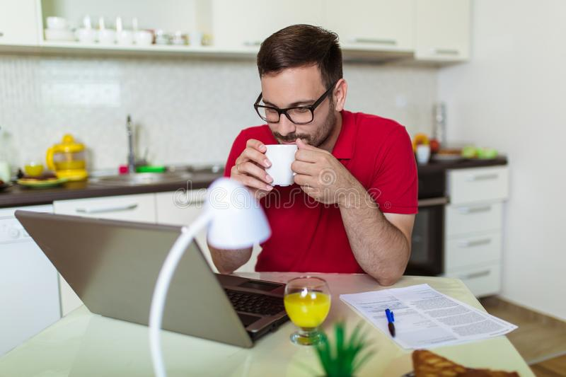 Young man, wearing glasses and smiling, as he works on his laptop to get all his business done early in the morning with his stock image