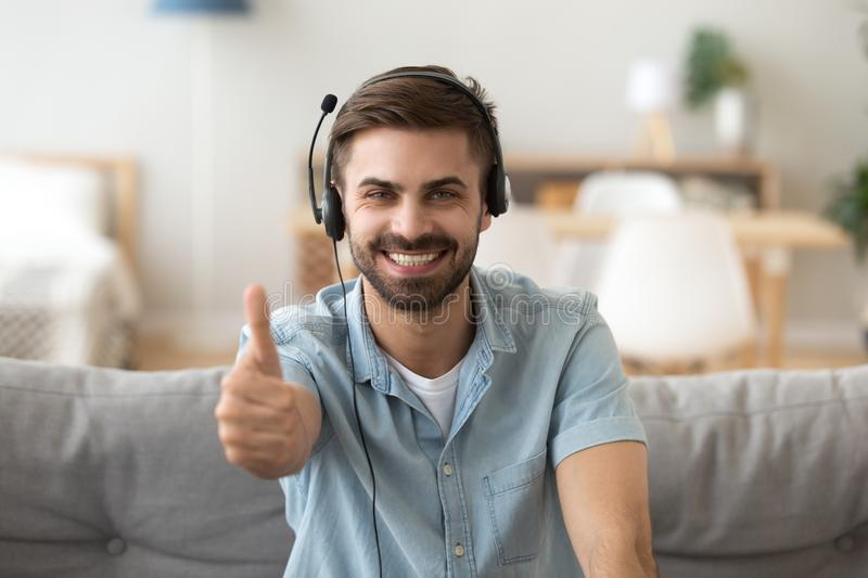 Happy young man wearing headset showing thumbs up giving recommendation. Friendly guy in headphones satisfied with good service like distance learning foreign royalty free stock photography