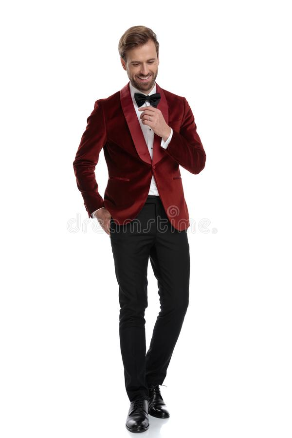 Happy young man wearing red velvet tuxedo and black bowtie royalty free stock photos