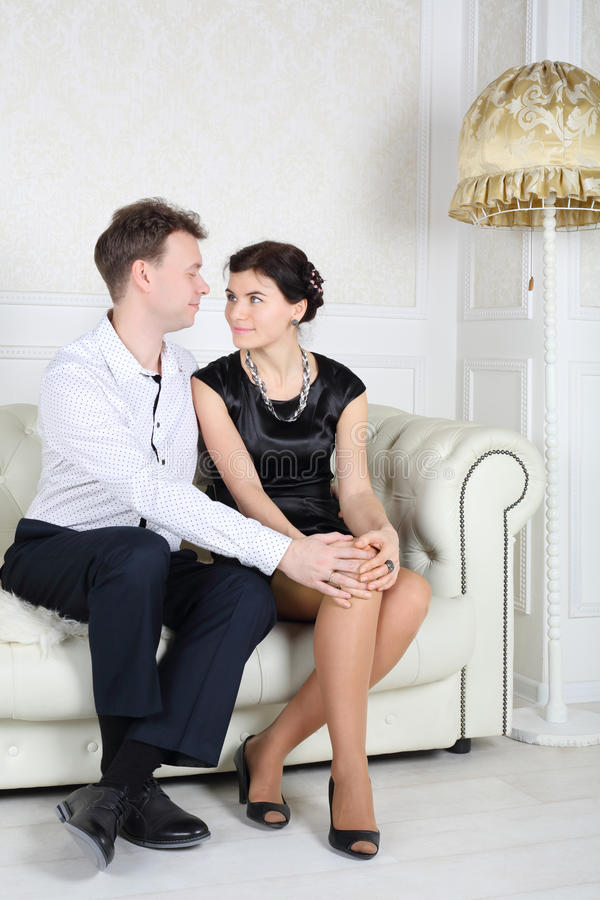 Happy young man and woman sit at sofa and look at each other. Happy young men and women sit at white sofa and look at each other in light room royalty free stock images