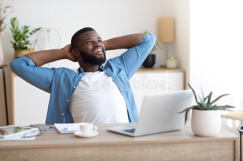 Happy young man working on laptop while sitting at his working place at home. Satisfied with work done stock image
