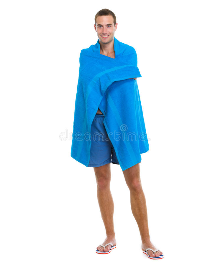 Happy young man wrapped in beach towel stock photos