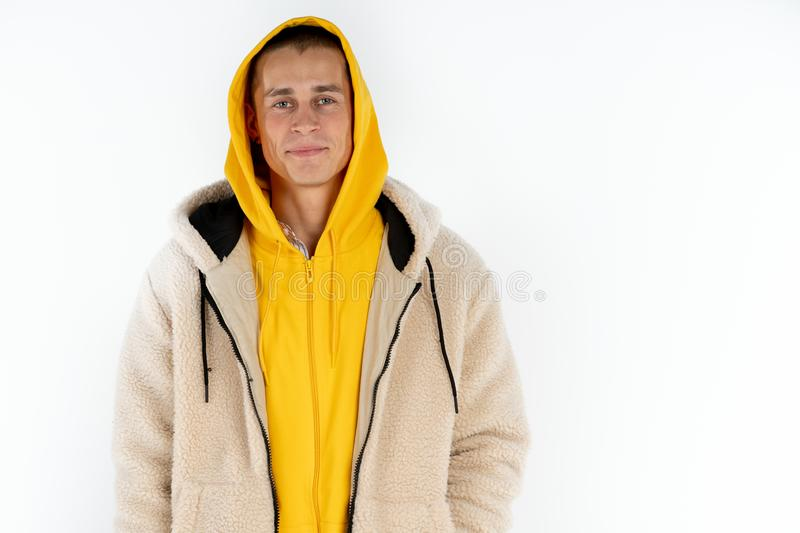 Happy young man in yellow hoodie isolated over white background, copyspace for your text stock photo