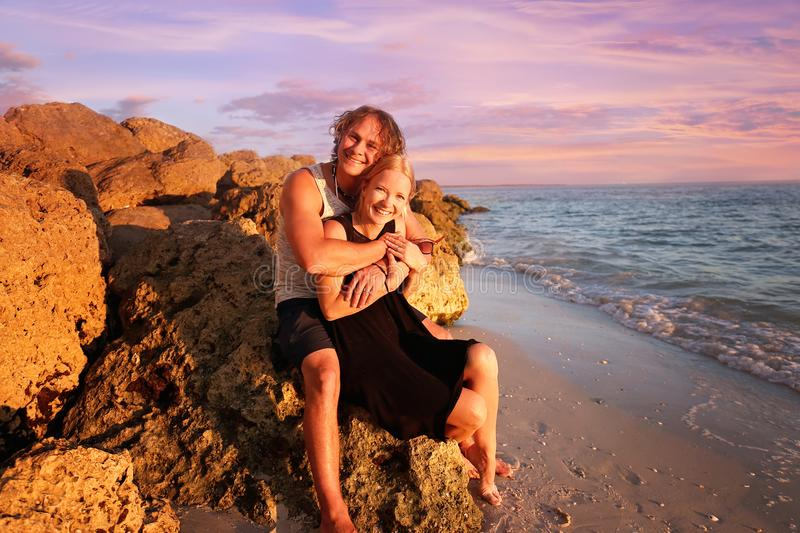 Happy Young Married Couple Sitting on Rocky Beach by the Ocean a royalty free stock photos