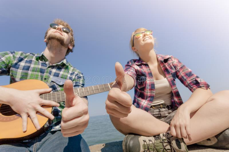 Young man hipster with guitar and woman. royalty free stock photography