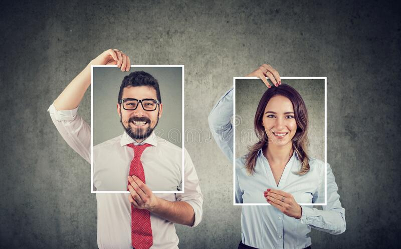Happy man and woman holding self portraits stock photo