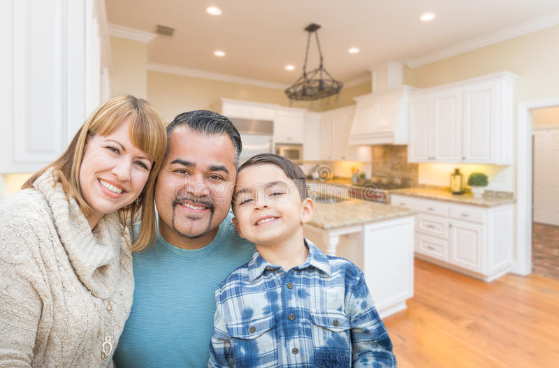 Happy Young Mixed Race Family in Custom Kitchen. Happy Young Mixed Race Family Having Fun in Custom Kitchen royalty free stock photography