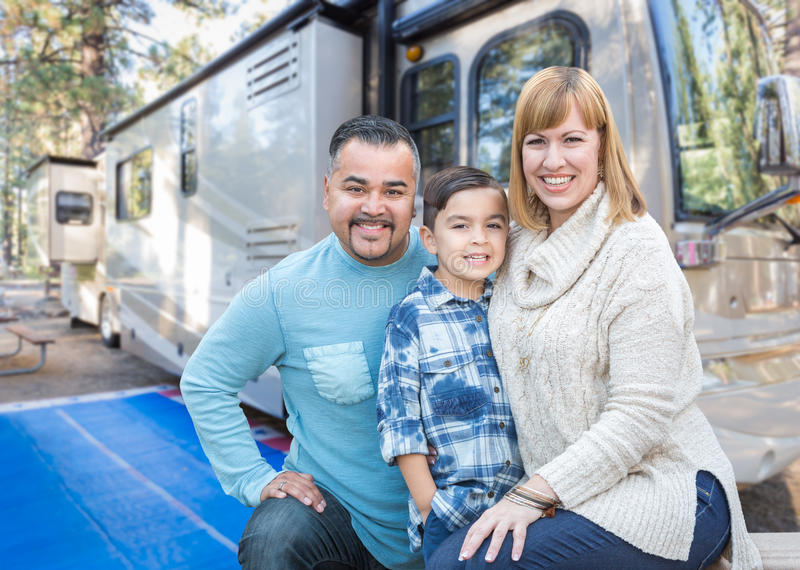 Happy Young Mixed Race Family In Front of Beautiful RV. Happy Young Mixed Race Family In Front of Their Beautiful RV At The Campground royalty free stock images