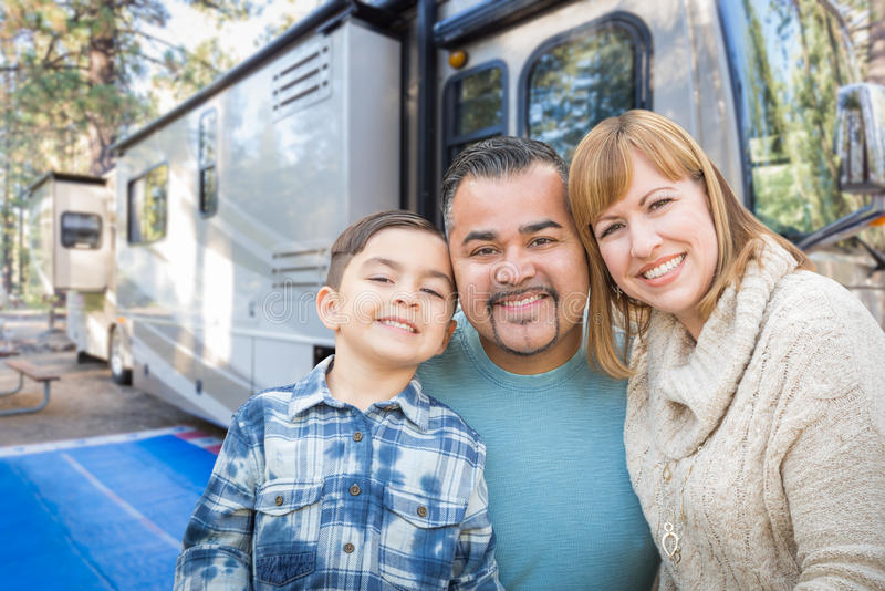 Happy Young Mixed Race Family In Front of an RV RV At. Happy Young Mixed Race Family In Front of Their Beautiful RV At The Campground stock photo