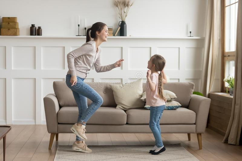 Happy mom and little kid daughter laughing dancing at home. Happy young mom baby sitter sister and cute funny little kid daughter laughing dancing in living room royalty free stock images