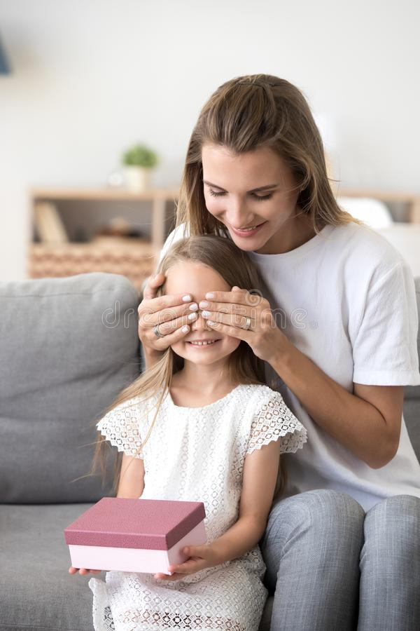 Happy mom closing daughter eyes presenting birthday gift stock images