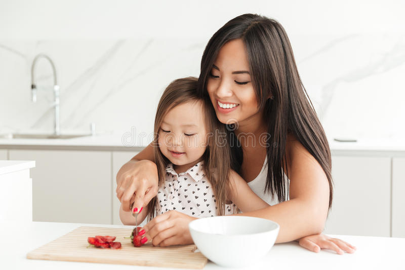Happy young mom with little cute asian daughter cut strawberry stock photos