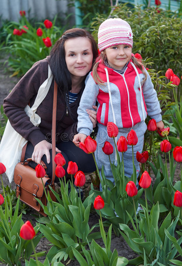 Happy young Mother with baby playing in a field of tulips stock images
