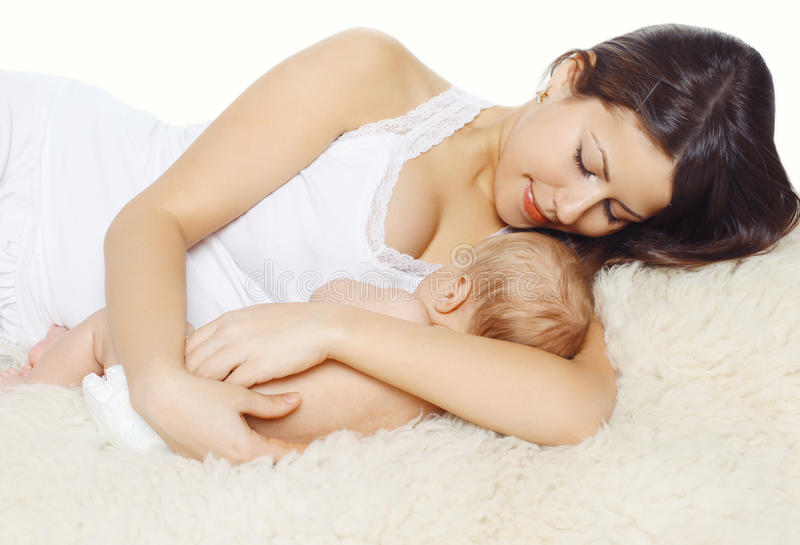 Happy young mother and baby sleeping together. On the fur royalty free stock photography