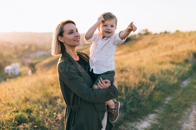 happy young mother carrying adorable little son pointing stock photos
