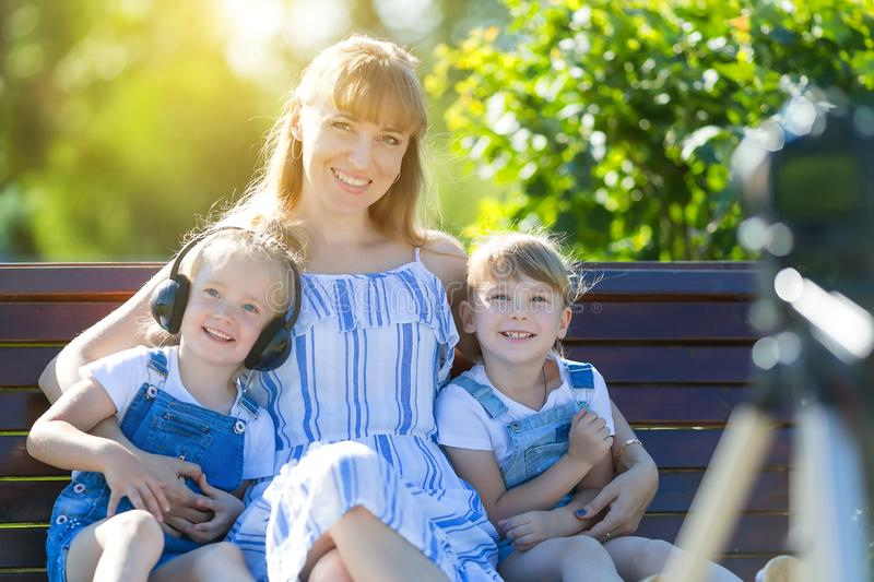Happy young mother with children in front of a video camera. A beautiful women with two daughters shot in a TV program, sits in front of a photo camera on a stock photo
